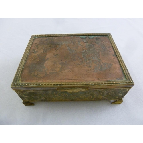 253 - A rectangular gilded metal musical jewellery casket with hinged cover on four bracket feet...