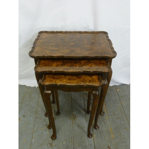 9 - A nest of three walnut tables on cabriole legs...