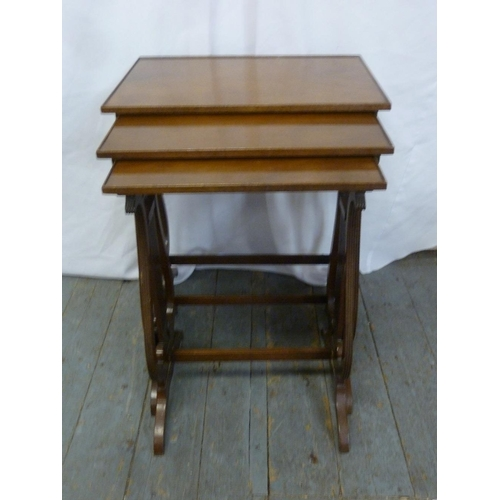 16 - A mahogany nest of three tables on scroll supports...
