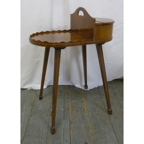 17 - An Edwardian mahogany shaped oval sewing table on four tapering rectangular legs...