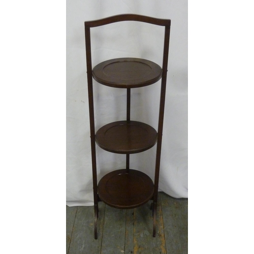 18 - A mahogany three tier plate stand of customary form...