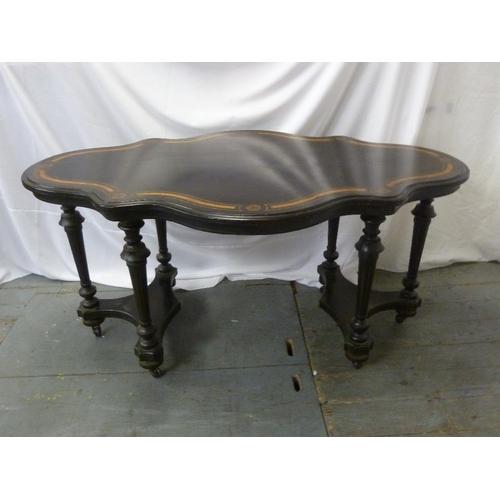 5 - A Victorian shaped oval ebonised table on six turned legs...