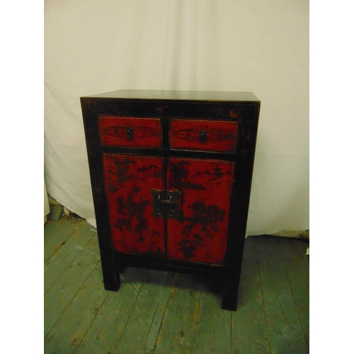 22 - An Oriental rectangular lacquered cabinet with two drawers and hinged doors...