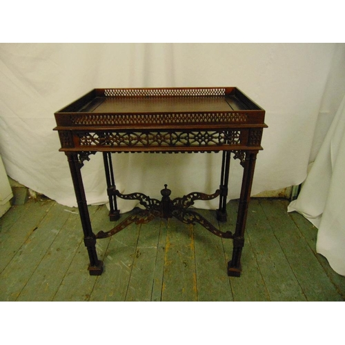 23 - An Oriental rectangular hardwood drinks table, scroll pierced gallery and sides on four stylised bam...