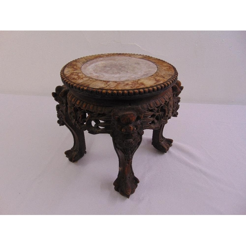 25 - A Chinese hardwood plant stand of circular form profusely carved with marble inset to the top...