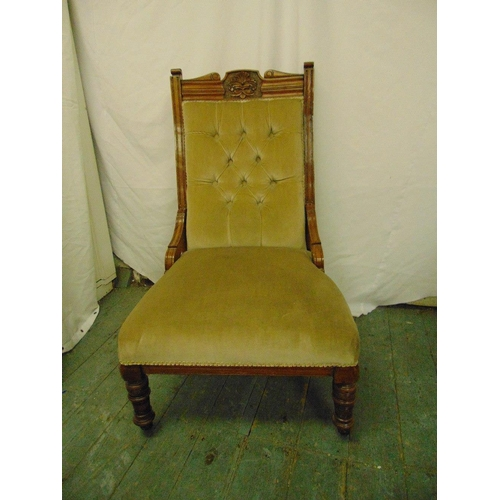39 - A Victorian mahogany upholstered button back chair on turned legs and original castors...