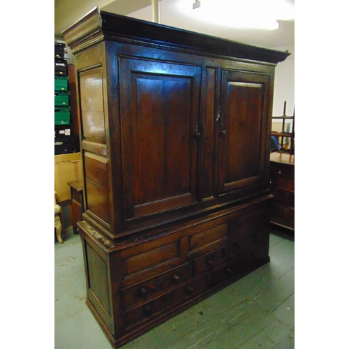 4 - An 18th century rectangular oak cupboard with hinged panelled doors, the plinth base with drawers...