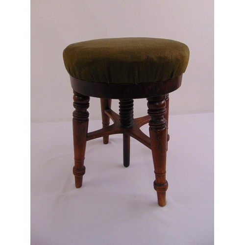 45 - An oak circular rise and fall piano stool on four turned legs...