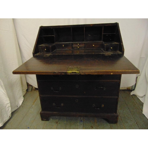 5 - A 19th century rectangular oak bureau, the hinged top above three drawers with brass handles, all on...
