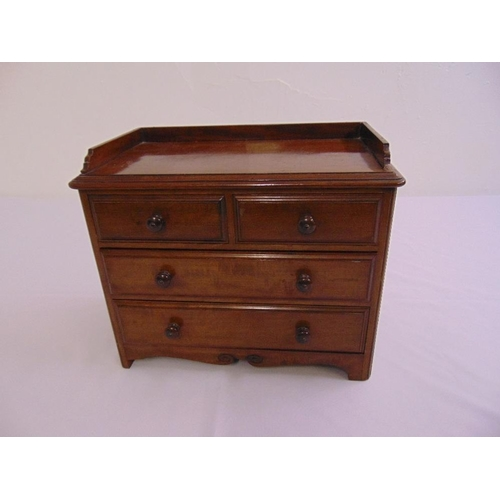 51 - A rectangular mahogany table-top apprentice chest of drawers with turned wooden handles...