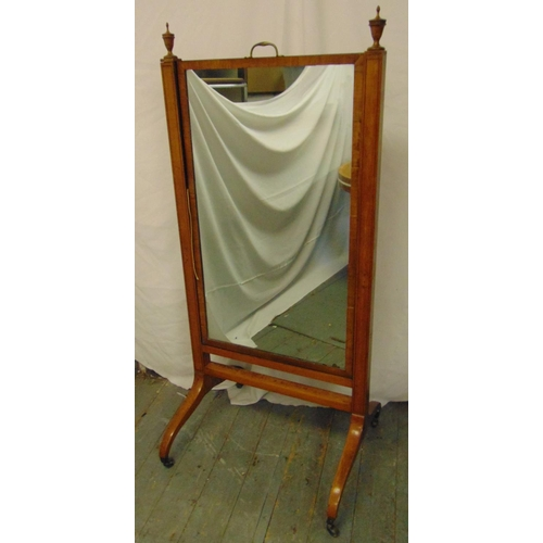 52 - A rectangular Cheval mirror, the supports surmounted with urn finials, on scroll legs with brass cas...