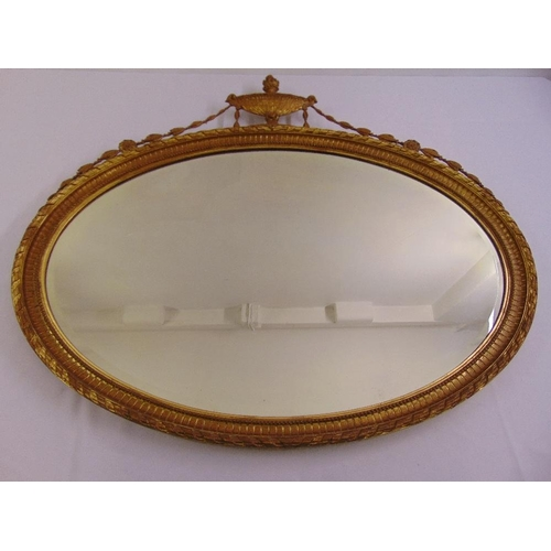 54 - A gilded neo-classical style oval mirror surmounted by an urn with husk swags...