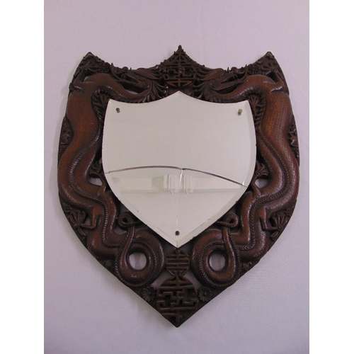 56 - A Chinese shield shaped wall mirror, the pierced hardwood frame carved with dragons, mirror A/F...