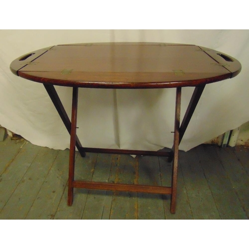 12 - An oval mahogany butlers tray with brass hinges on folding stand...