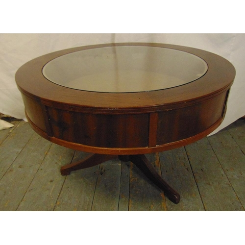 13 - A mahogany circular coffee table with glass display case to the centre on three outswept legs...