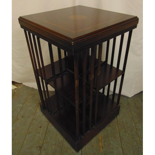 5 - An Edwardian rectangular revolving bookcase with inlaid top and slatted sides...