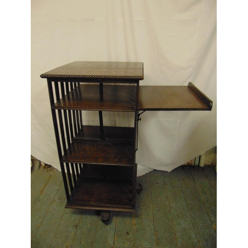 6 - An Edwardian rectangular revolving oak bookcase with slatted sides and drop flap reading table A/F...