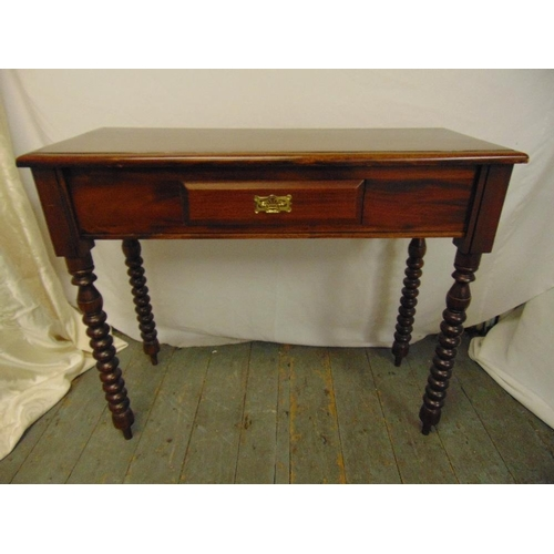 18 - A mahogany rectangular hall table on four turned legs the single drawer with brass swing handle...