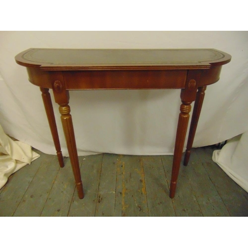 19 - A mahogany consol table shaped oval with inlaid tooled leather top on four tapering cylindrical legs...