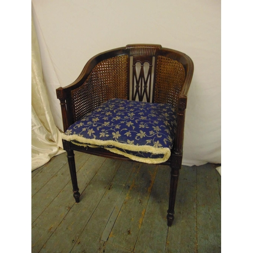 34 - An Edwardian mahogany occasional chair with bergere seat and back on four fluted cylindrical legs...