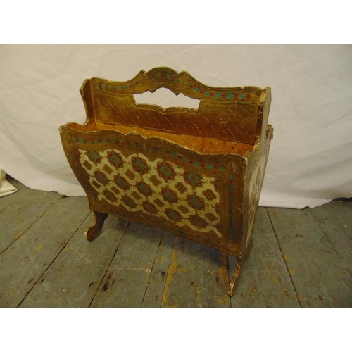 40 - A gilded Florentine wooden magazine rack on scroll legs with pierced carrying handle...
