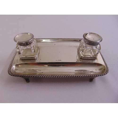 403 - A rectangular silver inkstand with rope twist border, two detachable glass inkwells with silver cove...