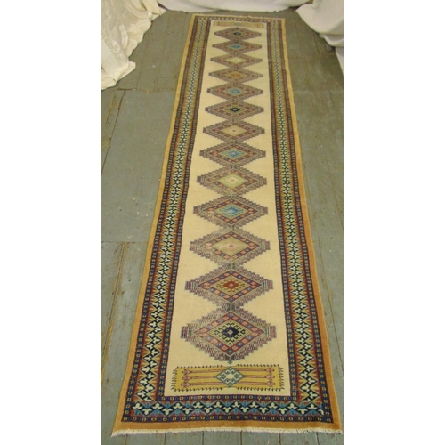 50 - A cream ground wool runner with repeating geometric pattern and border, 303 x 78.5cm...