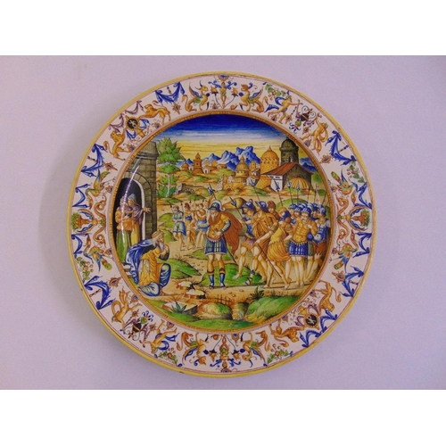 127 - A 19th century Italian faience majolica tin glazed earthenware charger depicting an army at the gate...