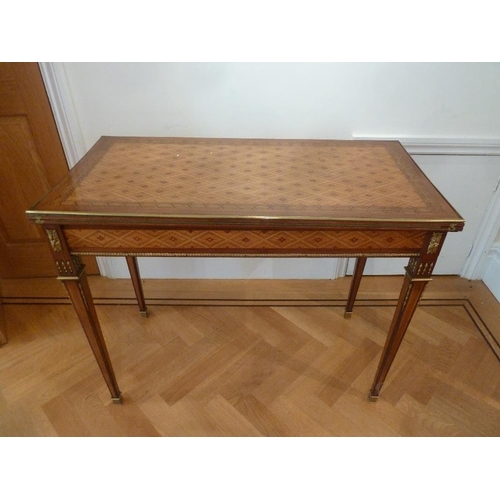 10 - A French Louis XVI style rectangular kingswood games table with gilded metal mounts on tapering rect...