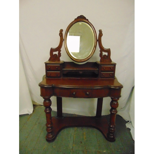 13 - A Victorian mahogany shaped rectangular dressing table with oval swivel mirror above five drawers on...