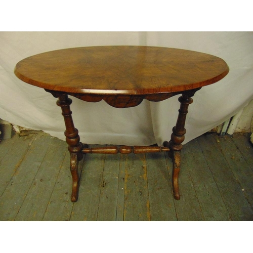 21 - A Victorian walnut and mahogany oval occasional table on turned columns and outswept legs...