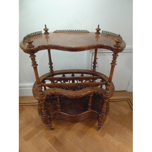 22 - A Victorian walnut and mahogany kidney shaped whatnot with turned columns on four supports with bras...