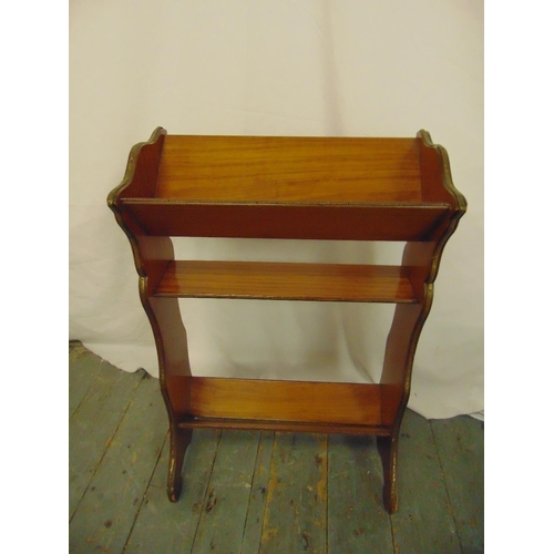 24 - A mahogany rectangular book stand with gilded metal mounts on four scroll legs...