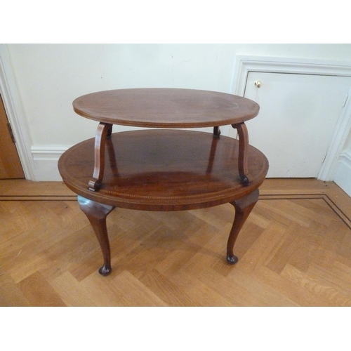 28 - An Edwardian oval two tier mahogany tea table on cabriole legs...