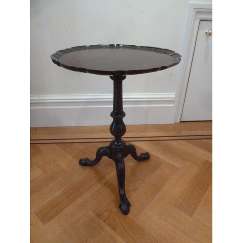 32 - A mahogany side table with pie crust circular border with baluster stem on outswept legs...