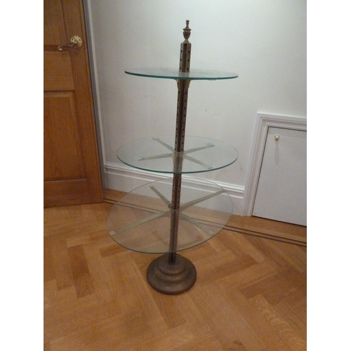 37 - A brass and glass three tier stand with urn finial on raised circular base...