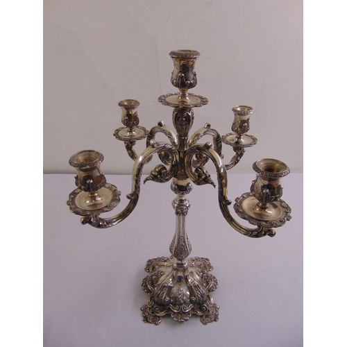 395 - A continental white metal four branch candelabrum, the leaf and shell chased baluster stem on raised...
