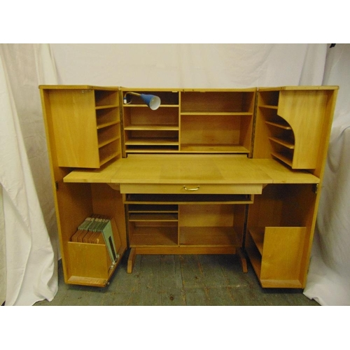 4 - A 1960s light oak rectangular desk cum cupboard, the hinged doors revealing book and stationery shel...