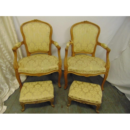 43 - A pair of French style upholstered armchairs and a pair of matching foot stools...
