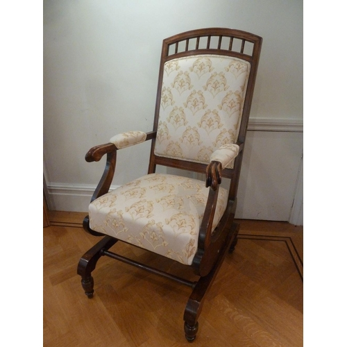 45 - An Edwardian mahogany upholstered rocking chair on four turned supports...