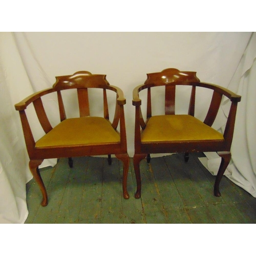 47 - A pair of mahogany armchairs with upholstered seats, slatted backs, on cabriole legs...