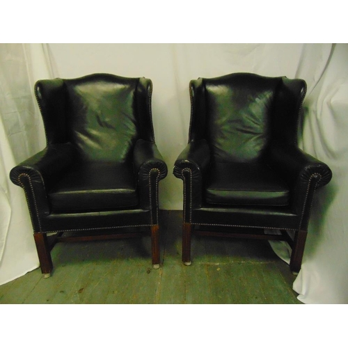 49 - A pair of black leather armchairs on fluted rectangular mahogany legs...
