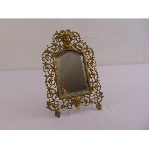 55 - A late Victorian shaped rectangular table mirror in scroll pierced brass frame with hinged strut...