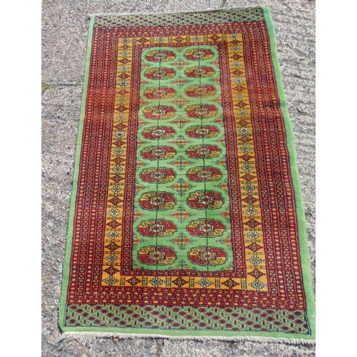 57 - Persian wool carpet green ground with repeating motif design, predominately red and green border wit...