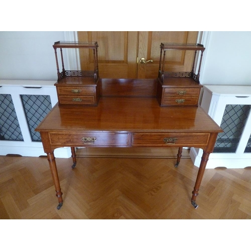 6 - A mahogany Chinese style rectangular desk with gallery on turned cylindrical legs with castors...
