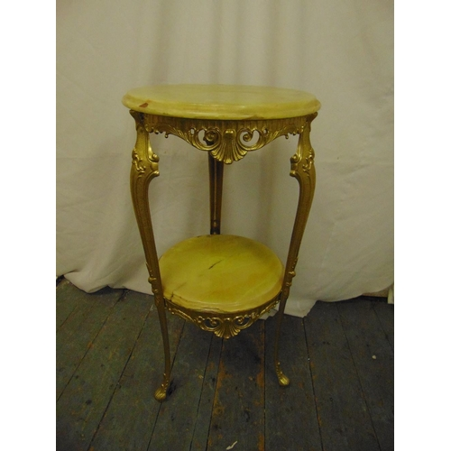 11 - An onyx and gilded metal side table, circular with scrolling supports...