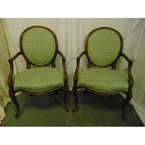 17 - A pair of French upholstered mahogany armchairs, oval backs, scroll arms and legs...