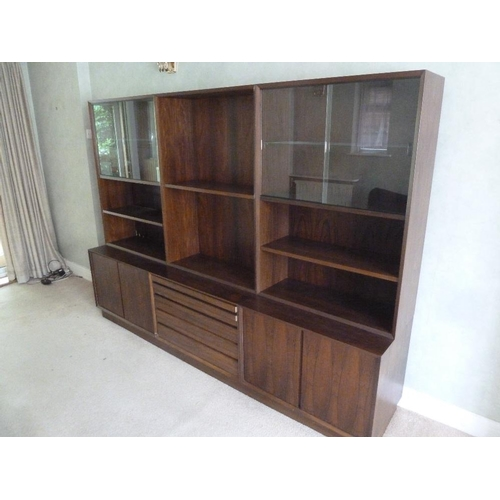 9 - Danish rosewood rectangular three section wall unit with cupboards and drawers on plinth base, to in...