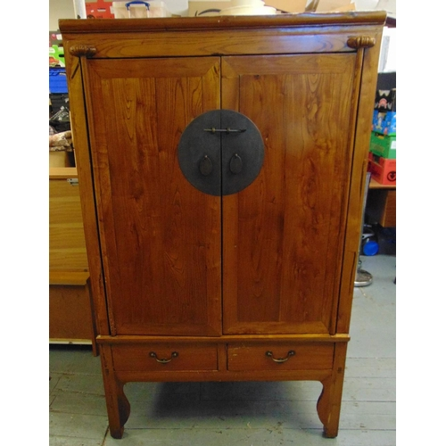12 - An oriental rectangular hardwood cabinet, the hinged doors with circular brass lock plate above two ...