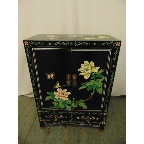15 - A Chinese rectangular black ebonised cabinet decorated with butterflies, flowers and leaves...